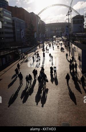 Persone che camminano con ombre scure lungo Wembley verso lo stadio di Wembley a Londra . Wembley SI FA National Football Stadium in Inghilterra