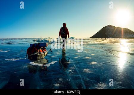 Donna con una mazza e trekking pole è sul ghiaccio del lago Baikal. Foto Stock