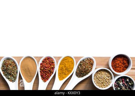 Varie spezie e erbe aromatiche in cucchiai snd bowles il piano portapaziente in legno isolato su bianco Foto Stock