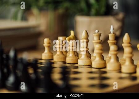 Vecchia scacchiera impostata per un nuovo gioco sul tavolo. Messa a fuoco selettiva su bianco pezzi di scacchi