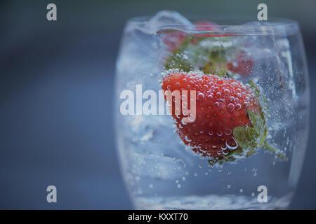 Rinfrescare cibi e bevande macro close up immagine fotografia di frutta rossa fragola in un bicchiere di cubetti di ghiaccio e frizzante acqua naturale con uno spazio Foto Stock