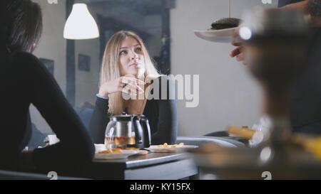 Giovani donne amici parlano in cafe, il cameriere ti porta burger
