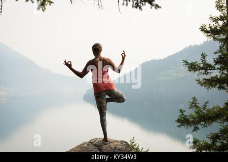 Montare la donna in equilibrio su una gamba sul bordo di una roccia Foto Stock