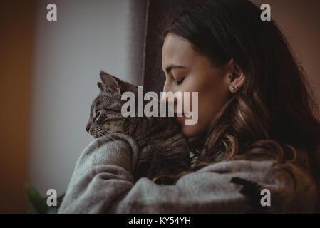 Close-up di bella donna annusare il suo gatto di casa Foto Stock