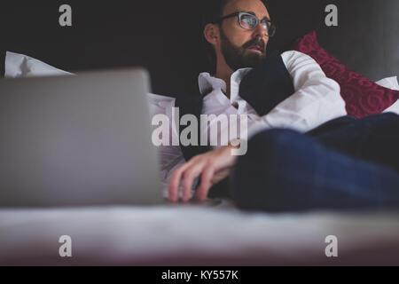Uomo d affari con computer portatile sul letto Foto Stock