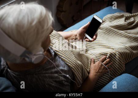 Senior donna ascoltando musica in cuffia mentre si utilizza il telefono cellulare