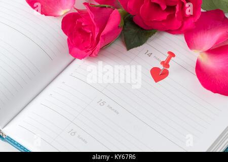 Il calendario il giorno di San Valentino pin rosa e rose rosse sul calendario notebook. amore concetto di appuntamento Foto Stock