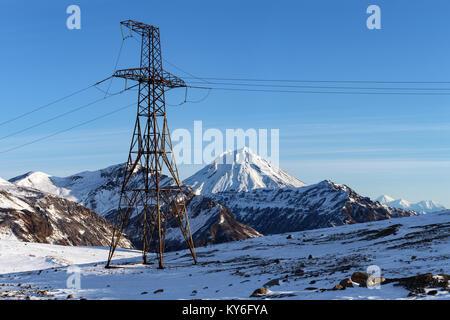 Tensione alta torre di metallo nelle Highlands di sunny inverno meteo. Vista sulla linea elettrica ad alta tensione Foto Stock