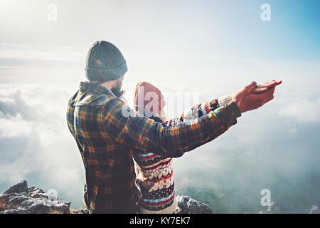 Giovane uomo e donna tenendo le mani alzate sul vertice di montagna amore e viaggio felice emozioni sentimenti concetto Foto Stock