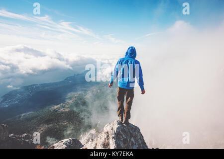 L'uomo viandante sulla scogliera di montagna gode di vista aerea oltre le nuvole stile di vita viaggio concetto Foto Stock