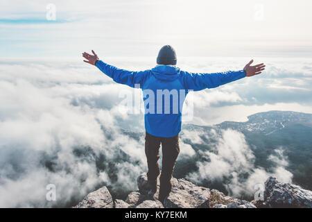Uomo sulla scogliera di montagna gode di vista aerea le mani sollevate oltre le nuvole stile di vita viaggio concetto Foto Stock