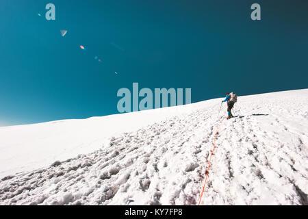 L'uomo la scalata al vertice della montagna sul ghiacciaio dello stile di vita di viaggio concetto avventura vacanze Foto Stock