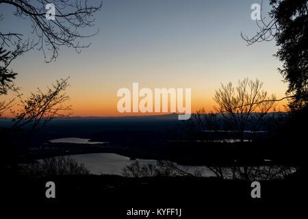 I colori caldi del tramonto, paesaggio nella stagione invernale con alpi all'orizzonte e laghi in primo piano Foto Stock