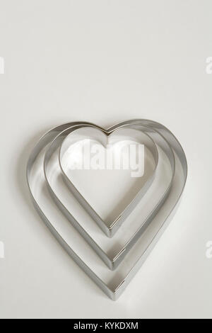 Un set di tre a forma di cuore ad cookie cutters su sfondo bianco Foto Stock