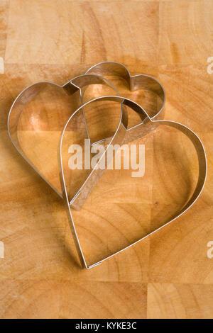 Un set di tre a forma di cuore ad cookie cutters su una cucina in legno sulla superficie di lavoro Foto Stock