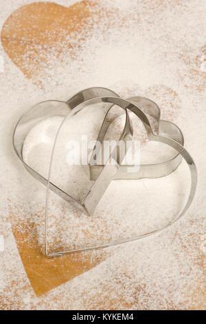 Un set di tre a forma di cuore ad cookie cutters su una spolverata di farina di sfondo Foto Stock