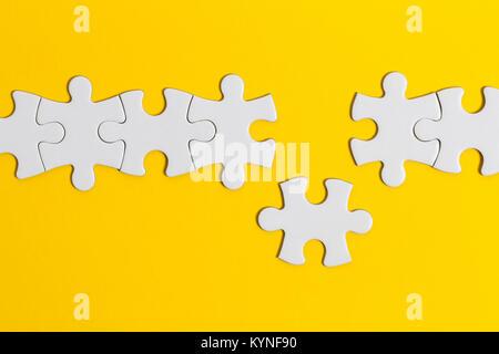 White jigsaw puzzle pezzi su uno sfondo giallo. Business del concetto di soluzione Foto Stock
