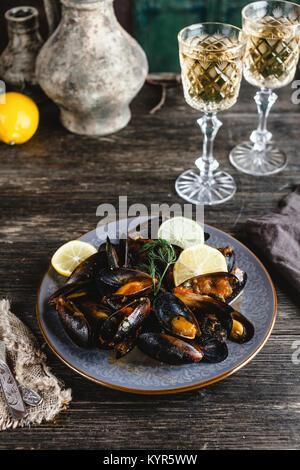 Cuocere le cozze con gusci servito sulla piastra con due bicchieri di vino bianco sul tavolo di legno Foto Stock