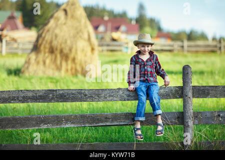 Little Boy in hat seduti sul recinto contro di pagliaio. Bambino su una copertura contro sfondo del paesaggio rurale. Giovani cowboy sorridendo timidamente e in cerca di un