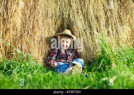 Felice ragazzo nel cappello di paglia seduta nel pagliaio, all'aperto, guarda la fotocamera. Bambino sorridente relax pagliaio su erba verde sotto il caldo sole. Giovane uomo spende ho