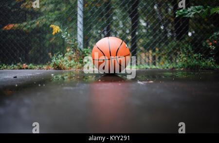Close-up della palla sul bagnato di basket contro la recinzione ad anelli