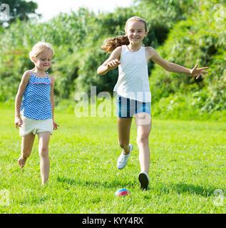 Due piccole ragazze felici giocando con la palla all'aperto, correndo insieme in estate park Foto Stock