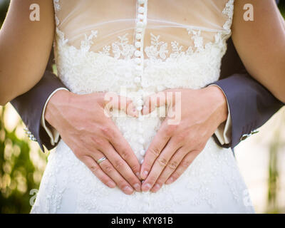 Lo sposo creazione di forma di cuore con le mani sul retro della sposa.matura nell'amore. Stretta di mano. Coppia Foto Stock
