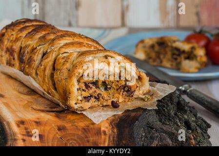Rotolo di maiale - salsiccia piccante di carne con peperoncino e fagioli in pasta sfoglia sul tavolo di legno Foto Stock