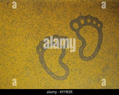 Due piedi su giallo di pavimentazione di sicurezza Foto Stock