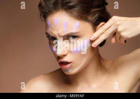 La risoluta donna fare il trucco con correttore. Foto di bella bruna donna su sfondo marrone. Cura della Pelle concept Foto Stock