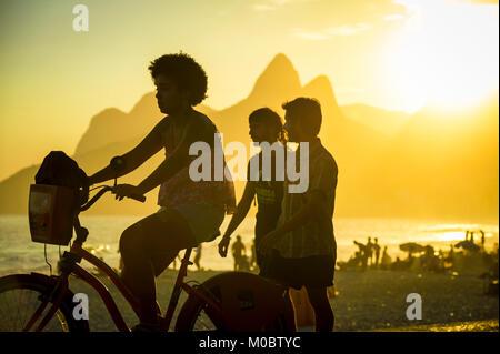 RIO DE JANEIRO - MARZO 20, 2017: i visitatori passano lungo la spiaggia di Ipanema di Arpoador, un posto popolare per prendere il tramonto contro due fratelli di montagna.
