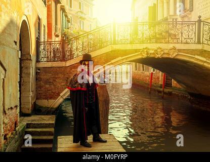 L uomo non identificato in costume nero, cappello e maschera in posa di fronte del piccolo ponte veneziano sul stretto Foto Stock