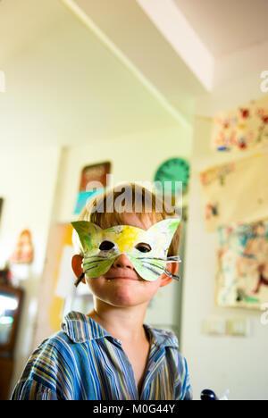 Una chiusura di un sorridente tre anni di ragazzo nel suo pigiama indossando un handmade maschera gatto in una cucina Foto Stock