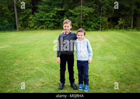 Due ragazzi in piedi sul prato con la mano su ogni spalla vestita in formalwear - sorridente, facendo divertimento, Foto Stock