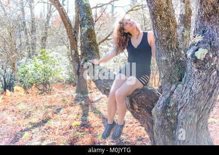 Giovane donna felice seduta di arrampicata sul ramo di albero su escursione autunnale in pantaloncini corti cercando Foto Stock