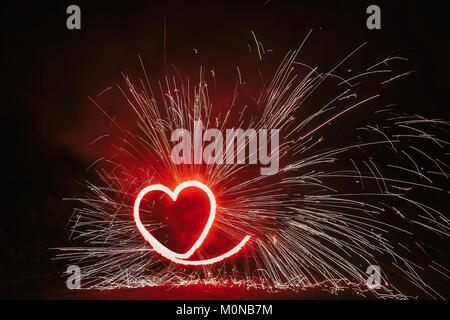 Rosso a forma di cuore con fuochi d'artificio brilla su sfondo nero nella notte. Buon San Valentino card. Bengala a fuoco che arde nel cuore. spazio per il testo o per matrimoni