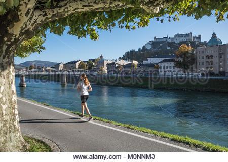 Salisburgo, Joggerin an der Salzach, im Hintergrund die Festung Hohensalzburg, fare jogging lungo le rive del fiume Foto Stock
