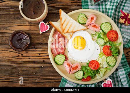 La prima colazione il giorno di San Valentino - uovo fritto a forma di cuore, toast, salsicce, pancetta e verdure Foto Stock