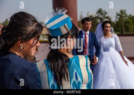 Un 'appena sposato' giovane arrivano al Registan complesso per le loro foto di nozze, il Registan, Samarcanda, Uzbekistan Foto Stock