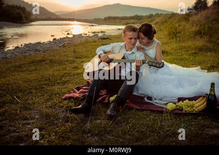 Matrimonio romantico ritratto durante il tramonto. Bello lo sposo è suonare la chitarra e la splendida sposa abbracciando Foto Stock