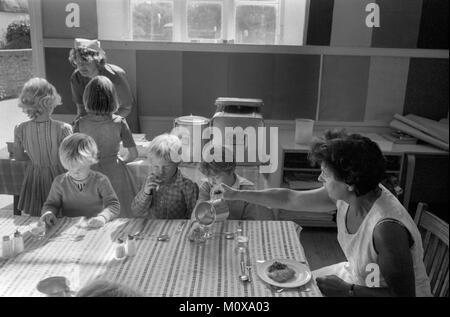 Villaggio scuola primaria degli anni settanta in Inghilterra. I bambini della scuola di sedersi insieme a un tavolo Foto Stock