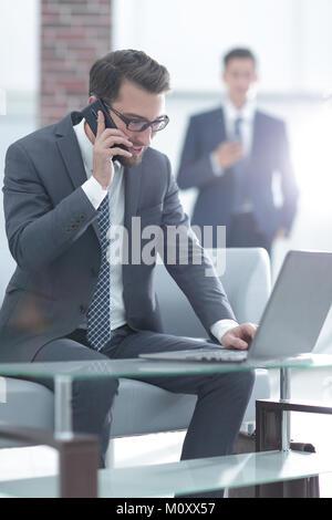 Ritratto di imprenditore parlando al telefono cellulare in ufficio Foto Stock