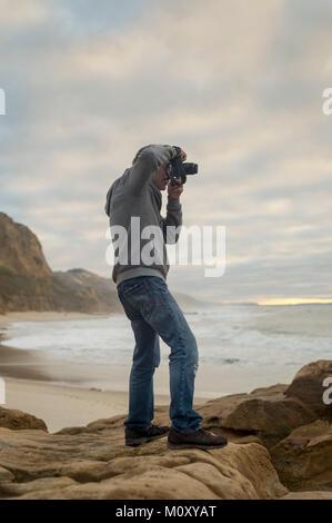 Uomo in piedi sulle rocce dalle coste scattare fotografie con la fotocamera reflex digitale. Foto Stock