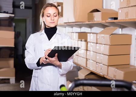 Sorridente femmina europea lavoratore carrello di trasporto delle scatole di cartone in deposito Foto Stock