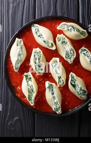 Deliziosa pasta conchiglioni ripieni di spinaci e ricotta con salsa di pomodoro close-up su una piastra. Verticale Foto Stock