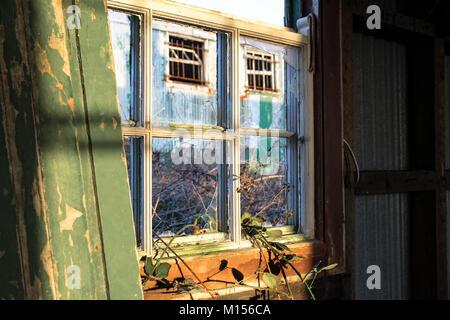 La luce del sole che splende su vecchio rotto la finestra in vetro Foto Stock