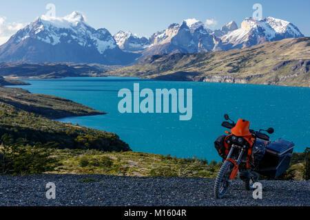 A fortemente pranzo motociclo su una strada di ghiaia dietro il Lago del Torro e il gruppo montuoso Cordillera Paine,Torres de Paine, Foto Stock