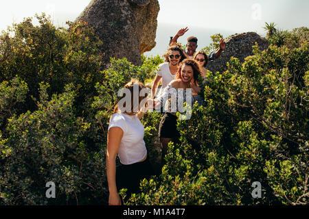 Gruppo di amici a piedi attraverso un sentiero di montagna su un giorno d'estate. Giovani escursioni in montagna. Foto Stock