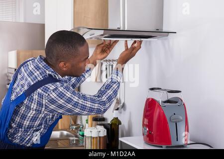 I giovani africani di fissaggio maschio cucina filtro estrattore in camera con cucina Foto Stock