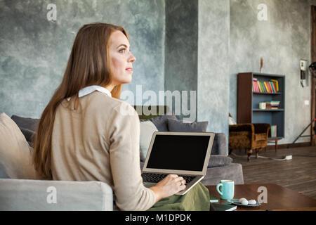 Lo schermo del laptop sulla donna sfocata e sfondo interni Foto Stock